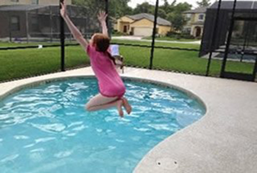 picture of girl jumping into pool at 6 Bed Home at Cypress Pointe Orlando Florida to Buy